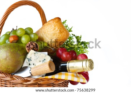 Wine, ciabatta, cheese, herbs, grapes and pear in a wicker basket for picnic. - stock photo