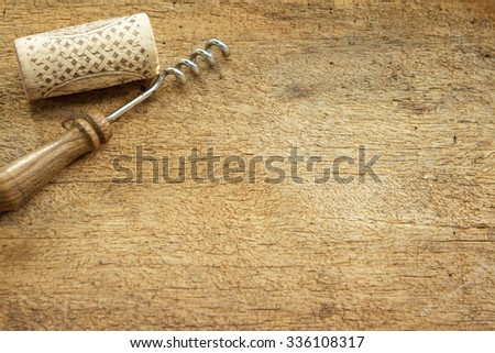 Wine cork and corkscrew on wooden table - stock photo