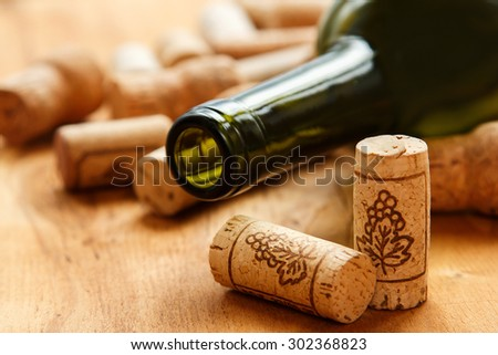 Wine corks and bottle on wooden table - stock photo