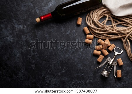 Wine, corks and corkscrew over dark stone background. Top view with copy space - stock photo