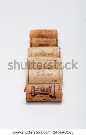 "Wine Corks lined up on white. You can read ""Mis en Bouteille a la caves"" on them which means ""Bottled in our caves"". In the back is written ""Villages 2010"" which means ""Village 2010"". - stock photo"