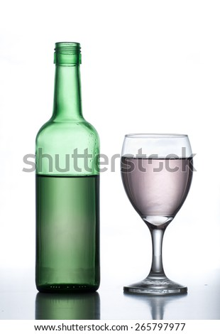 Wine glass and bottle on reflective surface with white background. - stock photo