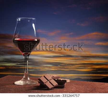 Wine glass and chocolate with colorful sunset - stock photo