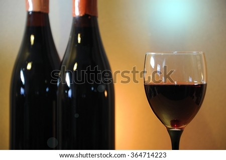 Wine glass and old bottles - stock photo