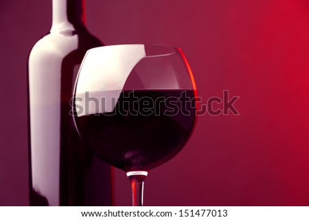 wine glass and wine bottle with red wine against colored background  - stock photo