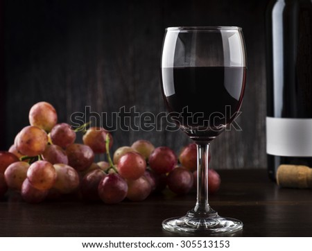 Wine glass , Bottle and Grapes on a wooden background - stock photo