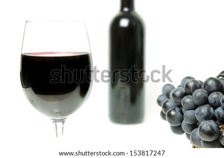 Wine glass close view with grapes and a bottle on the background - stock photo