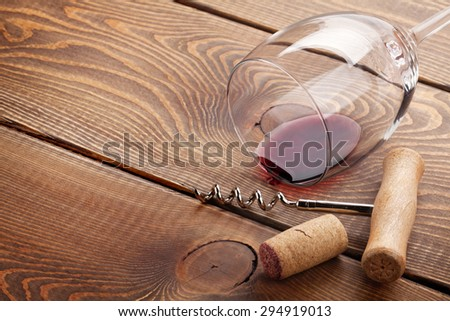 Wine glass, cork and corkscrew over wooden table with copy space - stock photo