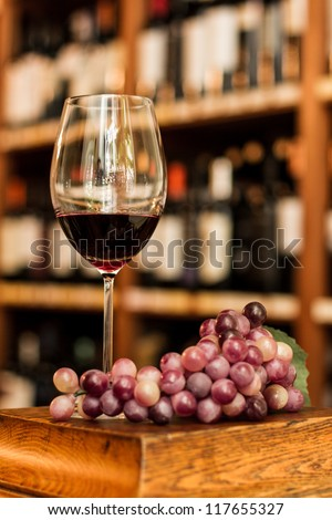 Wine glass, grape and bottles on the background. - stock photo