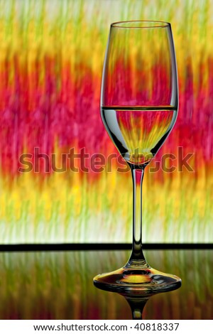 Wine glass in front of lighted background showing colors of pink, yellow and green - stock photo