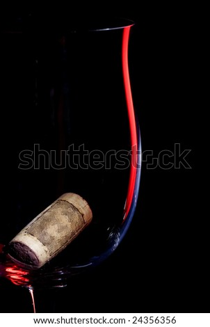 Wine glass object  in low key style with cork over black background. - stock photo