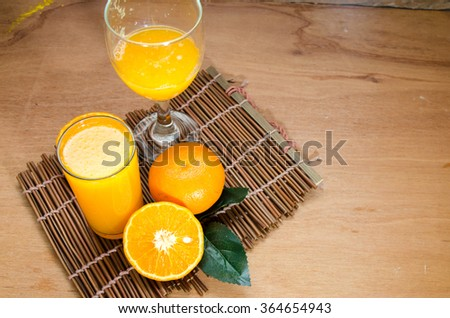 Wine glass of freshly pressed orange juice with on wooden table - stock photo