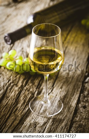 Wine. Glass of white wine in wine cellar. Old white wine on wood. - stock photo
