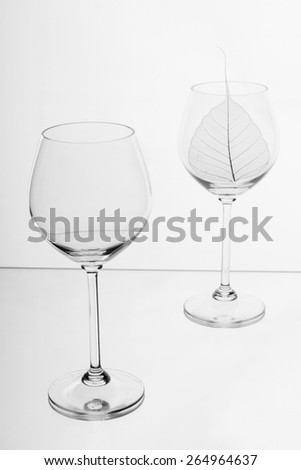 Wine glass with a leaf. On a white background - stock photo