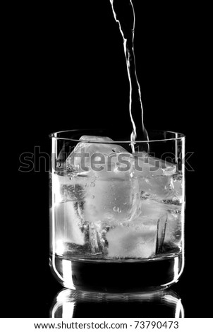 Wine glass with alcohol dropping into it. Black background. Studio shot. - stock photo