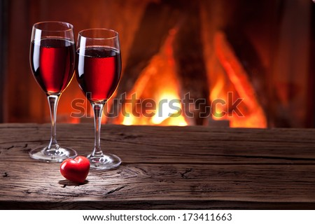 Wine glasses and a heart on the background of the fireplace. - stock photo