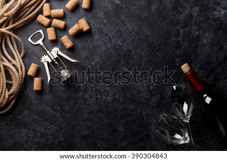 Wine, glasses and corkscrew over stone background. Top view with copy space - stock photo