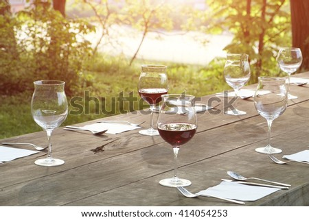 wine glasses on a wooden table outdoor in the countryside - stock photo