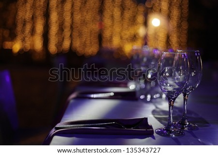 Wine glasses set on a dinner table at a wedding. - stock photo