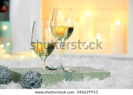 Wine glasses with Christmas decor on fireplace background - stock photo