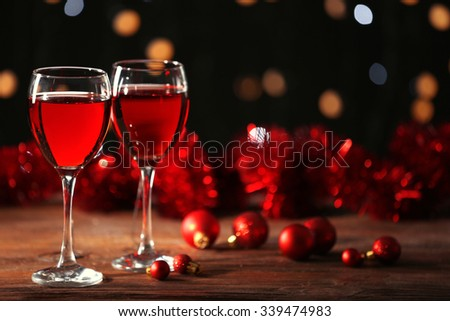 Wine glasses with Christmas decorations on wooden table - stock photo