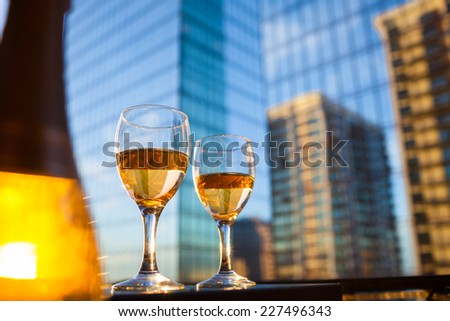 Wine glasses with modern city background - stock photo