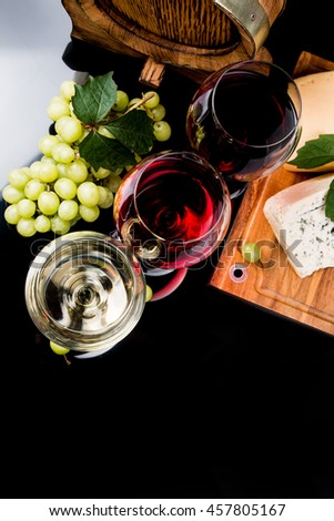 Wine glasses with red, white and rose. Cheese on black table with fresh grapes  - stock photo