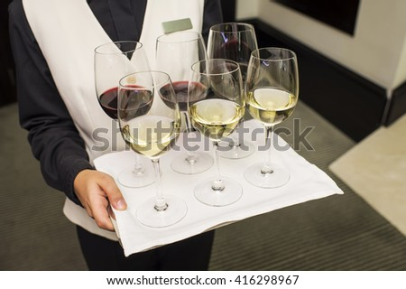 wine glasses with waiter on the tray - stock photo