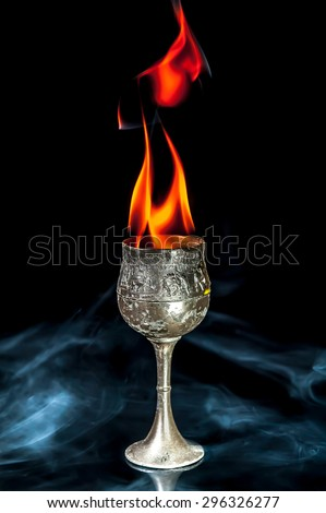Wine goblet with Fire flames with smoke on black background - stock photo
