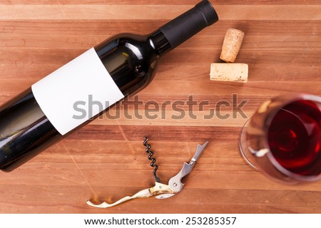 Wine in details. Top view of bottle and wineglass with red wine on the wooden table  - stock photo