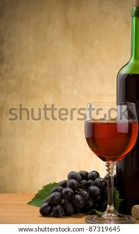 wine in glass and bottle with grape fruit on wood background - stock photo