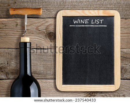 Wine list on blackboard and wine bottle on wooden background - stock photo