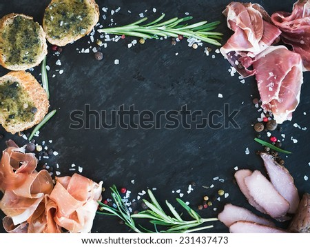 Wine meat appetizer set: prosciutto, serrano and cured lamb meat selection with spices, herbs and baguette slices with pesto on a dark stone background with a copy space in the center - stock photo