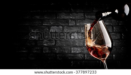 Wine pouring in wineglass near brick wall - stock photo