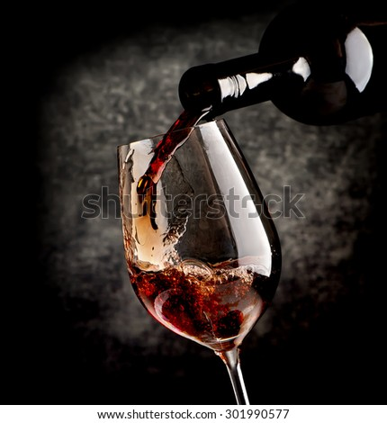 Wine pouring in wineglass on a black background - stock photo