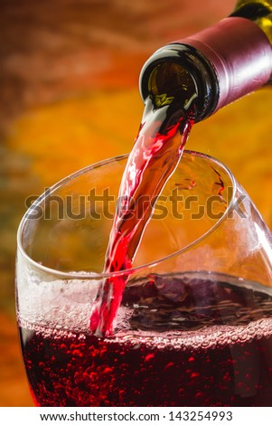 Wine pours into the glass of the bottle on a colored background - stock photo