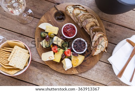 Wine tasting with delicious cheese platter on a wooden board, with figs, olives, strawberry, homemade jams, plain crackers and tasty bread. - stock photo