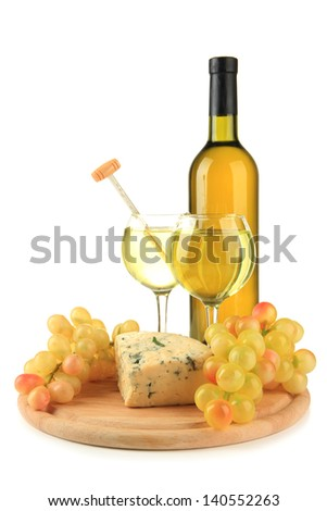 Wine, tasty blue cheese and grape on cutting board, isolated on white - stock photo