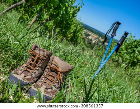 Wine Tourism-Pair of hiking shoes in the grass surrounded vineyards - stock photo
