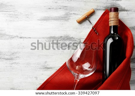 Wine with corkscrew on a light wooden background - stock photo