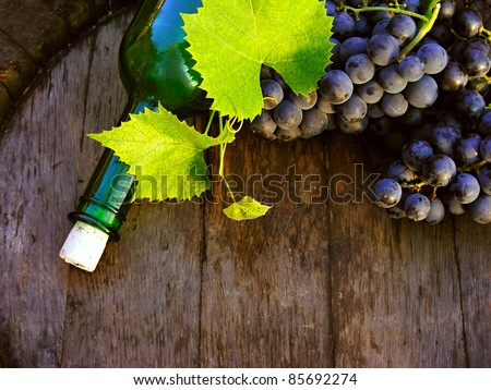 Wine with green bottle on a wooden barrel - stock photo