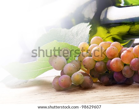 Wine with green bottle on a wooden table - stock photo