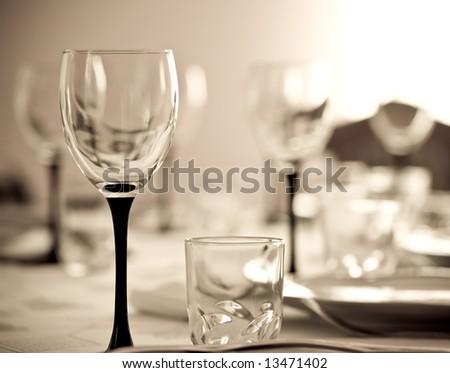 Wineglass against blurry background. Shallow DOF. Sepia tone. - stock photo
