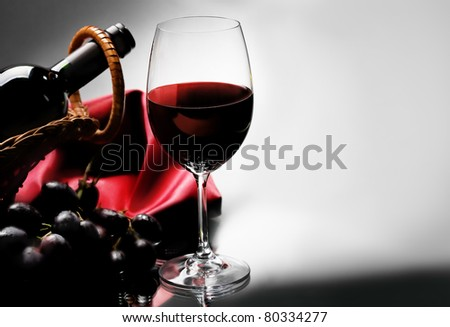 Wineglass and bottle of red wine in basket on black and white background. - stock photo