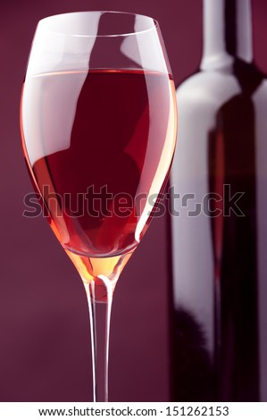 wineglass and bottle of rose wine against warm colored background  - stock photo
