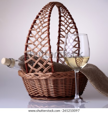 Wineglass and bottle of white wine in burlap in basket on white reflective background - stock photo