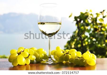 Wineglass and bunch of grapes against Geneva lake. Lavaux region, Switzerland - stock photo