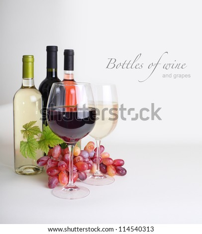 wineglass, bottles of wine and grapes - stock photo