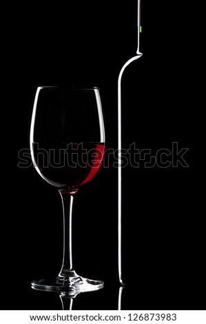 Wineglass of red wine and a bottle - stock photo