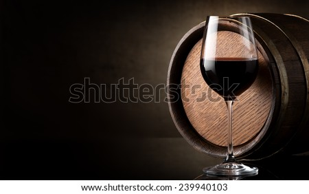 Wineglass of red wine and barrel on brown background - stock photo